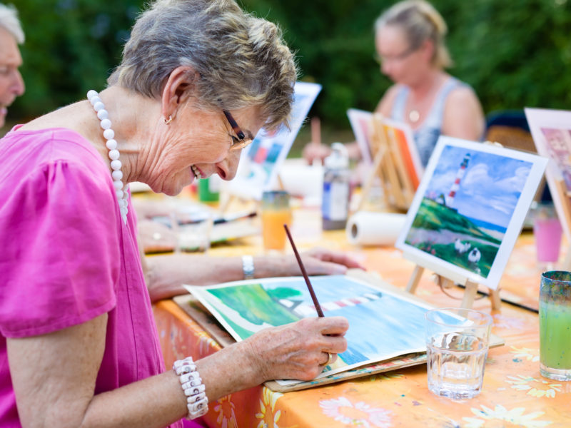 Side view of a happy senior woman smiling while drawing as a recreational activity or therapy outdoors together with the group of retired women.